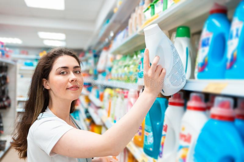 A young pretty woman pulls a cleaning agent from the shelf. Purchase and sale of goods in the store. Close up stock photos