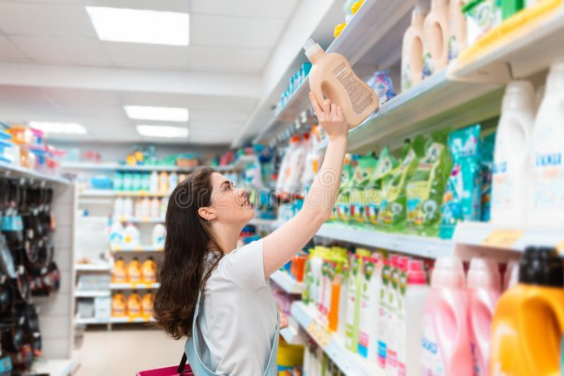 A young pretty woman pulls a cleaning agent from the shelf. Purchase and sale of goods in the store stock photo