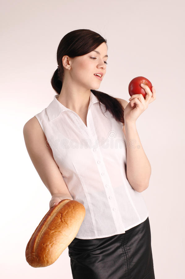 Young pretty woman with red apple and bread royalty free stock photo