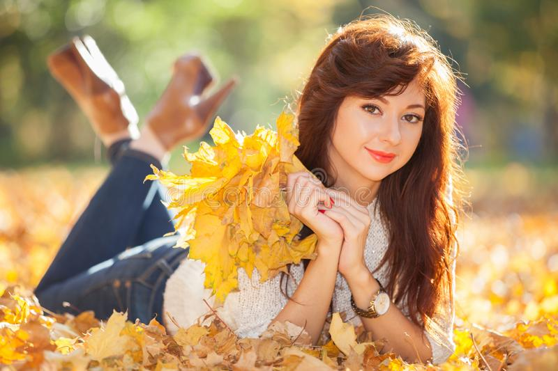 Young pretty woman relaxing in the autumn park. Beauty nature scene with colorful foliage background, yellow trees and leaves at stock photo
