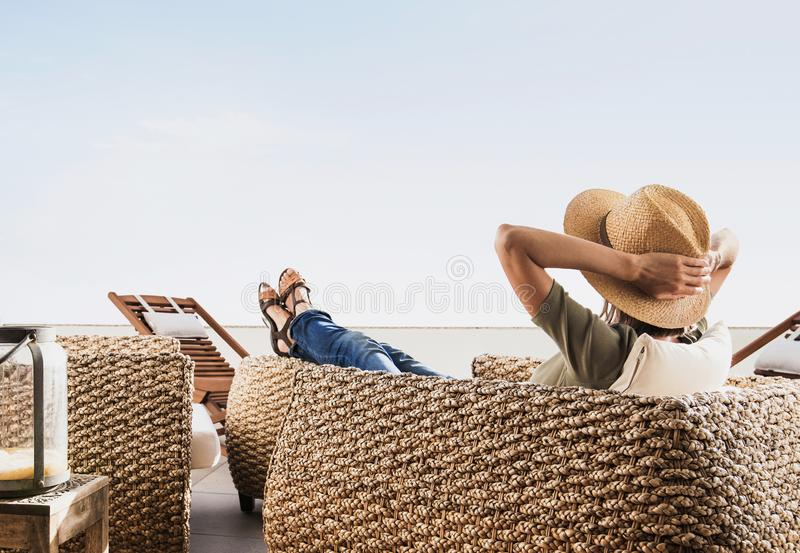 Young woman resting on hotel terrace. Vacations and summer fun concept. Beautiful girl enjoying life. Young pretty woman resting on hotel terrace. Vacations and royalty free stock images