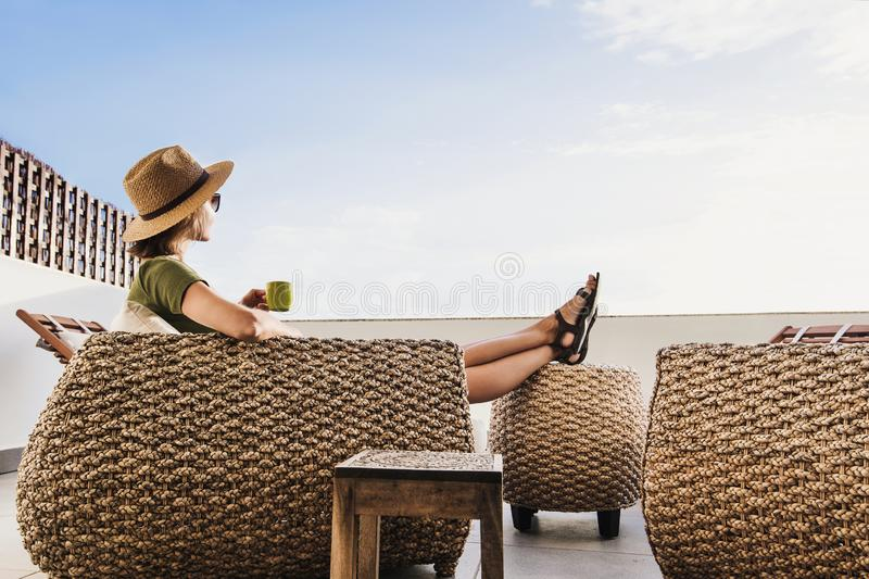 Young woman resting on hotel terrace. Vacations and summer fun concept. Beautiful girl enjoying life. Young pretty woman resting on hotel terrace. Vacations and royalty free stock image