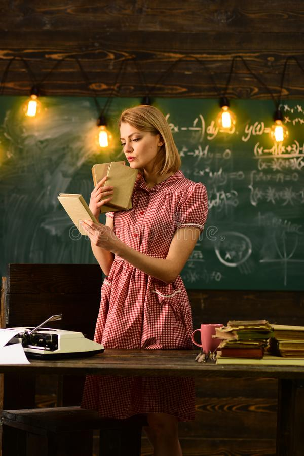 Young pretty woman at school blackboard near coffee cup and reading a book enjoys of rest. Dig into reading stock image