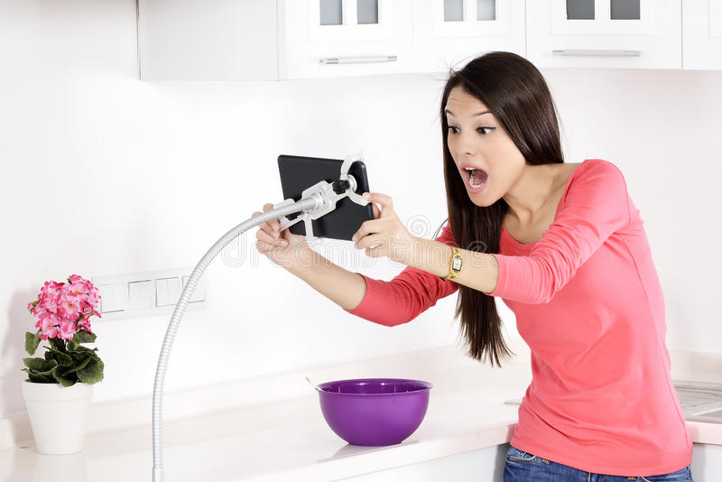 Young pretty woman shocked and looking at ipad stock photos