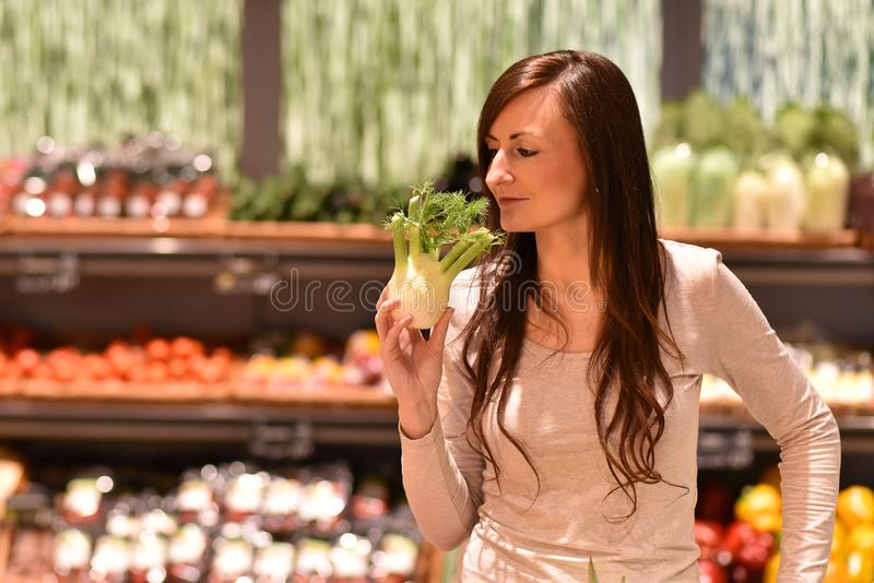 young pretty woman shopping for fresh healthy food in the supermarket royalty free stock image