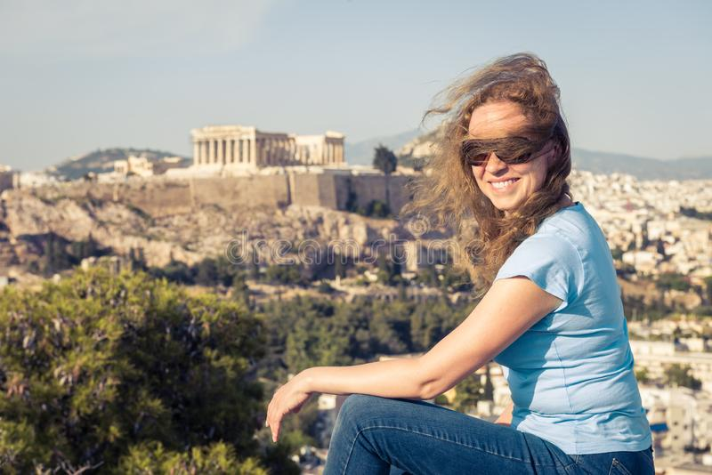 Young pretty woman sits at hilltop in Athens, Greece. Beautiful adult girl tourist smiles overlooking Athens city center royalty free stock photos
