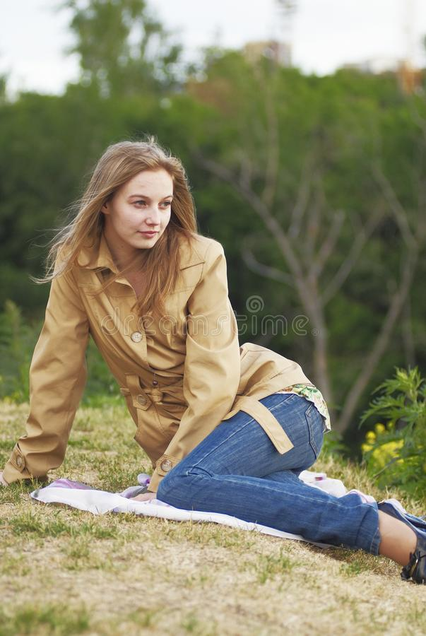 Young pretty woman sitting outdoors royalty free stock photography