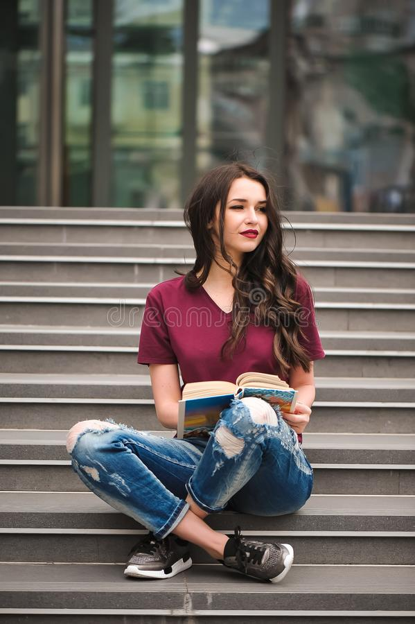 Young pretty woman sitting and reading a book enjoys of rest. stock image