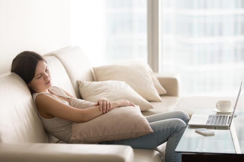 Young pretty woman sleeping on couch, taking nap on sofa royalty free stock photography