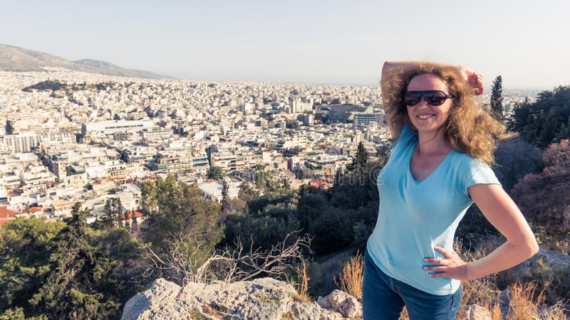 Young pretty woman smiles in Athens city, Greece. Beautiful female tourist poses overlooking Athens in summer stock photos