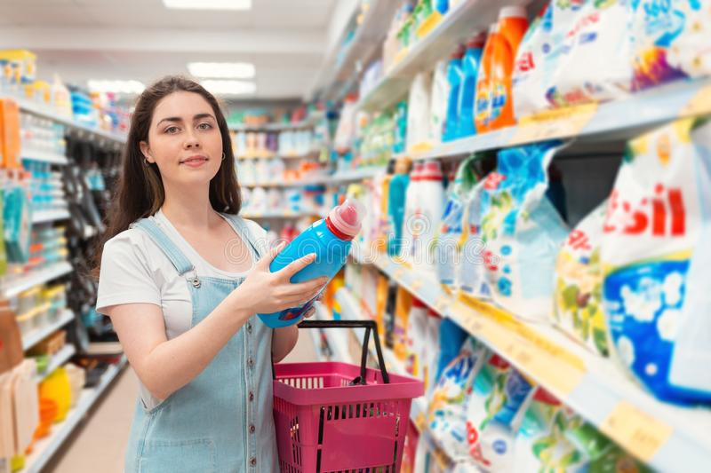 A young pretty woman smiles and chooses a cleaning agent in the store. Purchase and sale of goods in the store royalty free stock image
