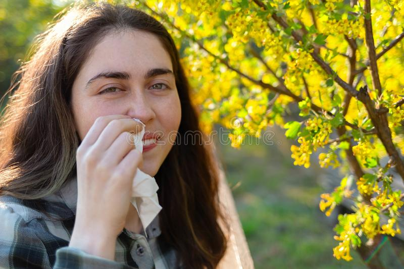 A young pretty woman smiles and is embarrassed by her Allergy to flower pollen. The concept of seasonal allergies and colds. Close. Up royalty free stock image
