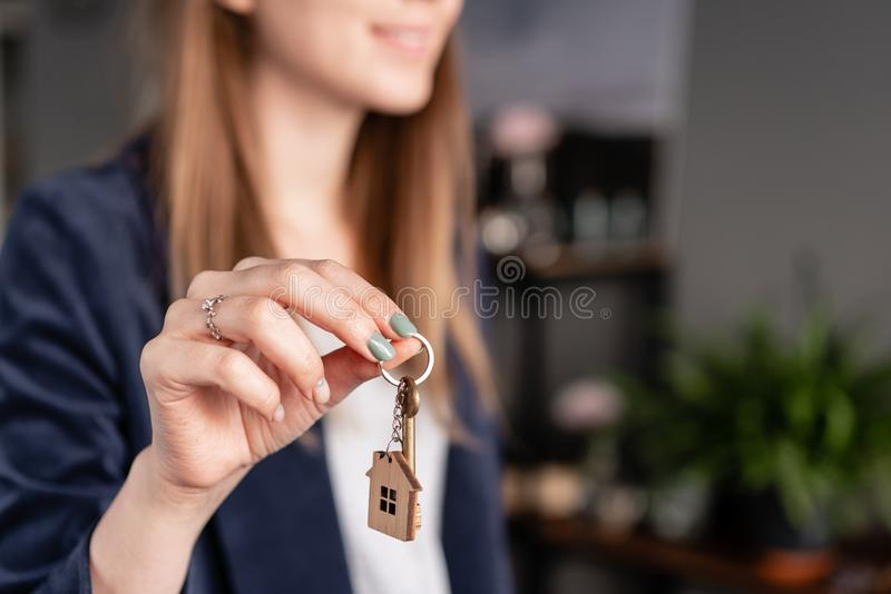 Young pretty woman smiles. House key in womans hands. . Modern light lobby interior. Real estate, hypothec, moving home stock photo