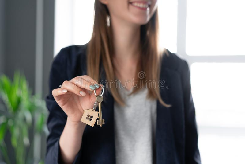 Young pretty woman smiles. House key in womans hands. . Modern light lobby interior. Real estate, hypothec, moving home royalty free stock photography
