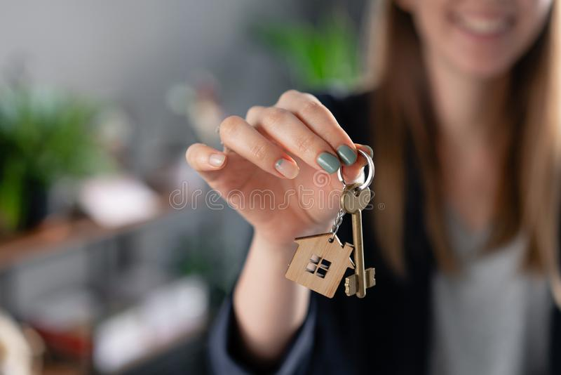Young pretty woman smiles. House key in womans hands. . Modern light lobby interior. Real estate, hypothec, moving home stock photos