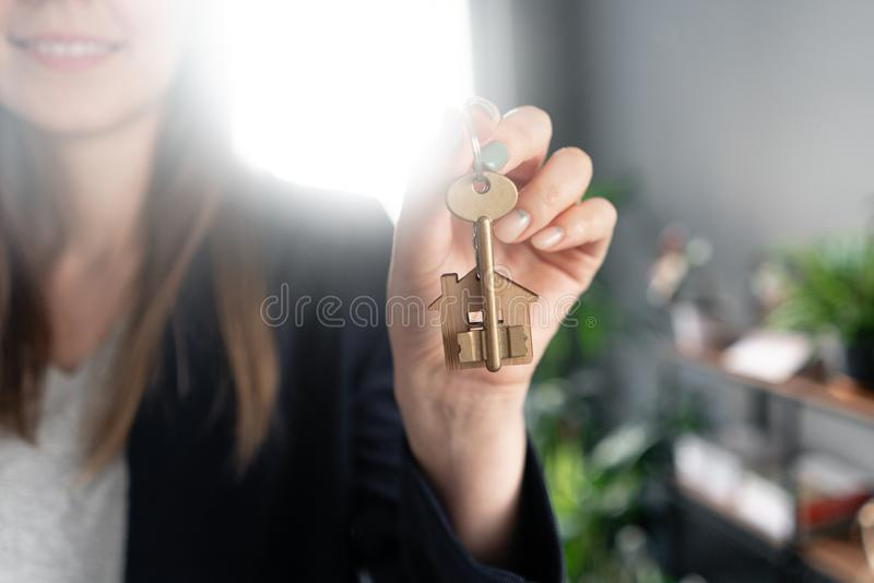 Young pretty woman smiles. House key in womans hands. . Modern light lobby interior. Real estate, hypothec, moving home royalty free stock photos