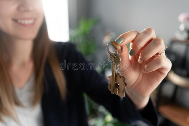 Young pretty woman smiles. House key in womans hands. . Modern light lobby interior. Real estate, hypothec, moving home royalty free stock images