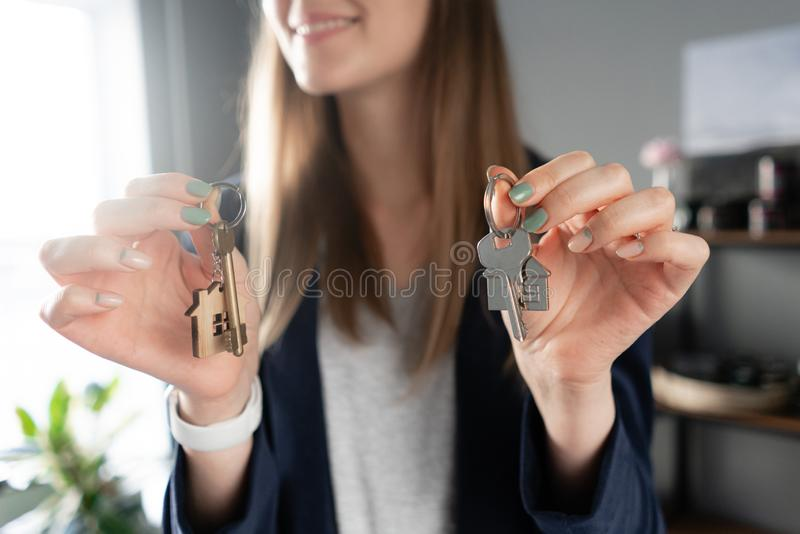 Young pretty woman smiles. House key in womans hands. . Modern light lobby interior. Real estate, hypothec, moving home stock images