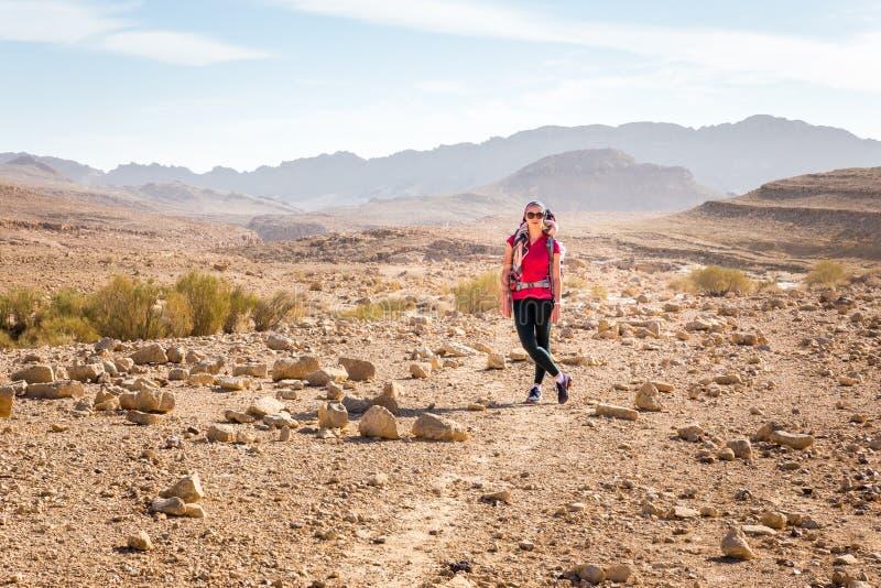 Young pretty woman standing stone desert trail, posing camera. Young beautiful pretty woman standing posing stone desert trail footpath, looking at camera, Arif stock photo