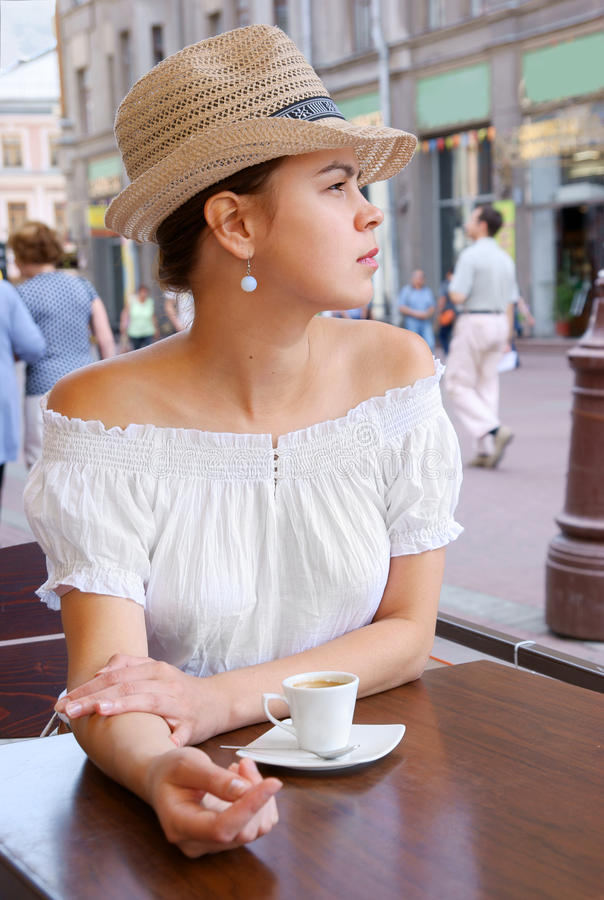 Young pretty woman in street cafe royalty free stock photo