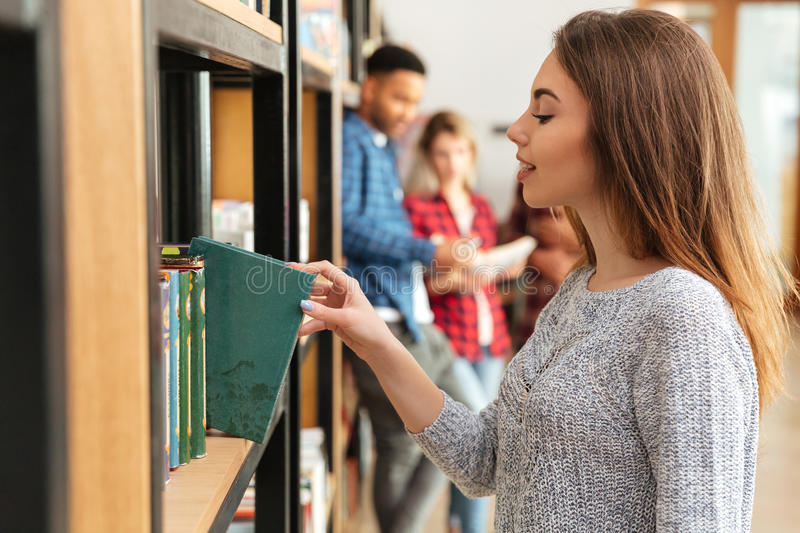 Young pretty woman student standing in library holding book. royalty free stock photos