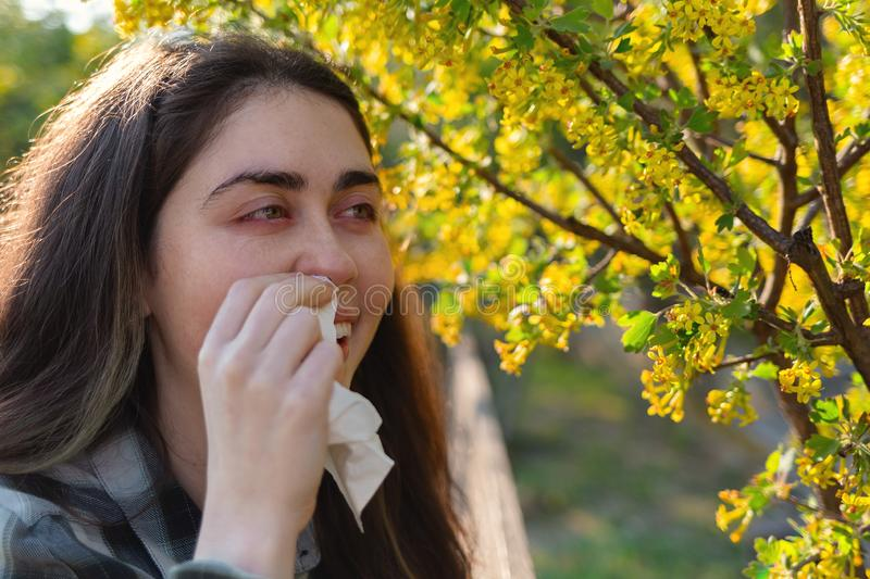 A young pretty woman is suffering from allergies. Red eyes and running snot. The concept of seasonal allergies and colds. Close up.  stock photos