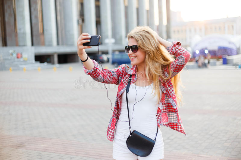 Young pretty woman taking a selfie at the square in the city. Summer holydays stock images