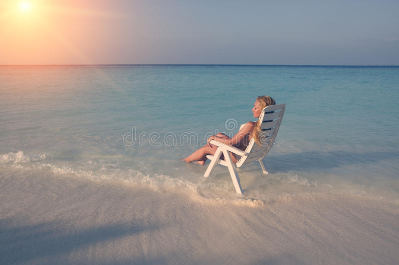 Young pretty woman tans in beach chair in sea , toning royalty free stock images