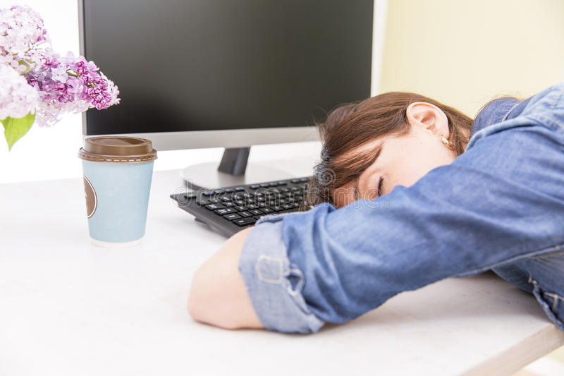 Young pretty woman tired and exhausted of work lying on table in front of computer and taking a break royalty free stock images