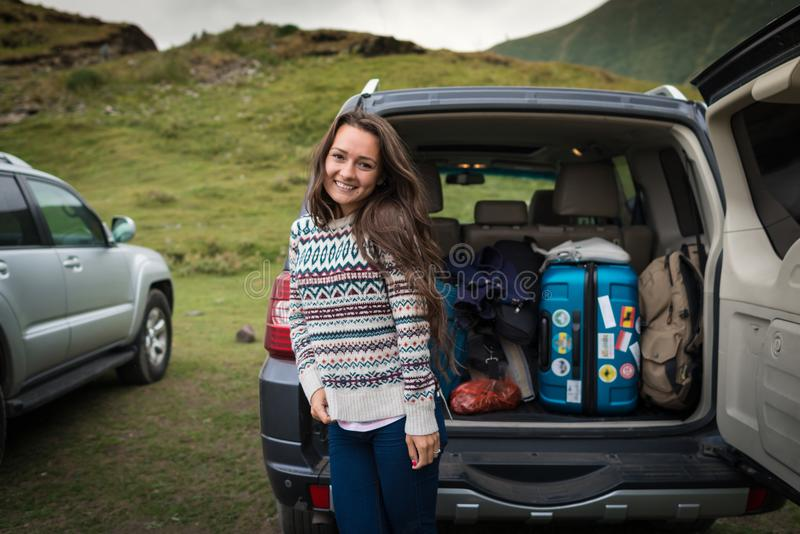 Young pretty woman traveler standing near open back door of the car stock photo