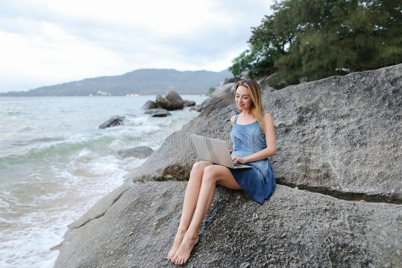 Young pretty woman using laptop and sitting on stone near sea, empty morning beach. stock photos