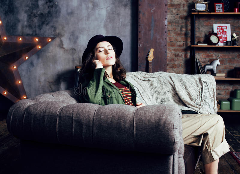 Young pretty woman waiting alone in modern loft studio, fashion musician concept, lifestyle people. Close up royalty free stock photography
