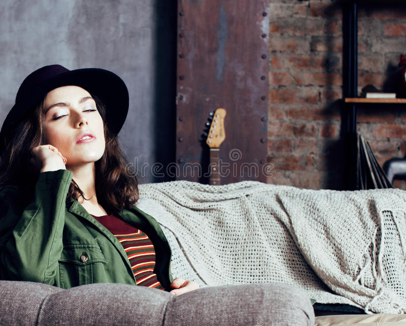 Young pretty woman waiting alone in modern loft studio, hipster in hat, fashion musician concept, lifestyle people. Close up stock photography