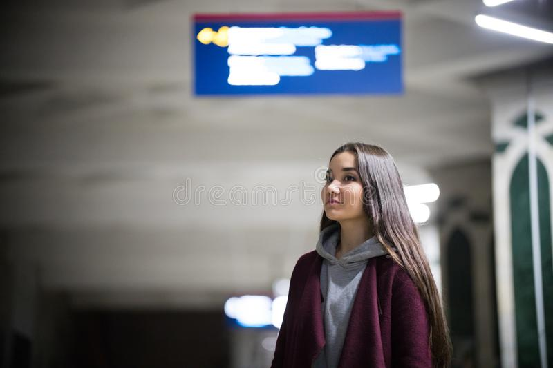 Young pretty woman waiting for the train in subway platform. Night. Smiling royalty free stock image