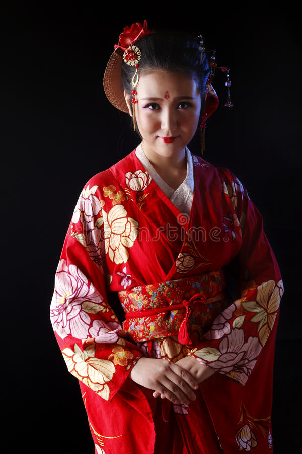 Young pretty woman wearing red kimono. On black background royalty free stock photos