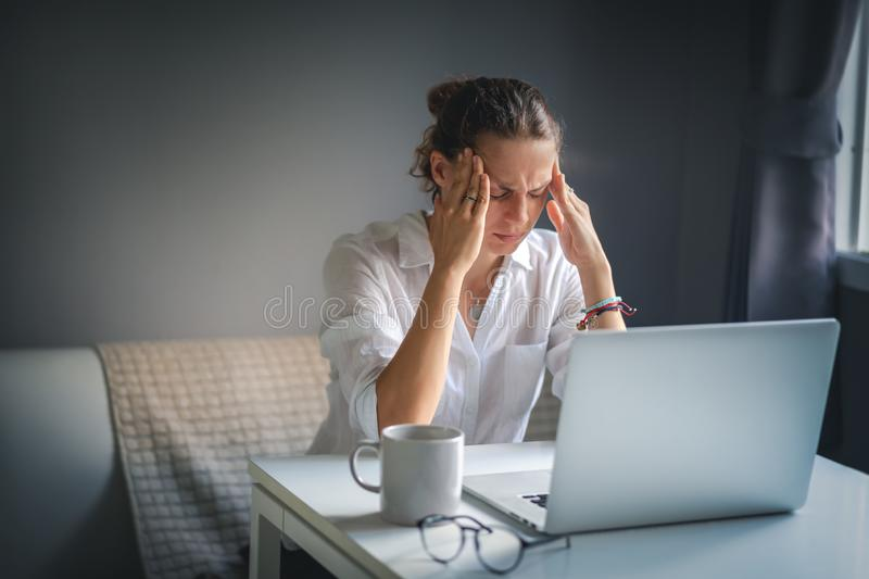 Young pretty woman in a white shirt sits at a table in front of a laptop, her eyes and head ache, workaholism, stress burnout.  stock photography