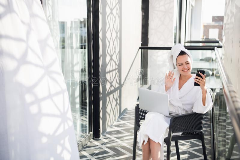 Young pretty woman in white soft bathrobe making selfie while relaxing on chair on outdoor terrace after swimming or stock photo
