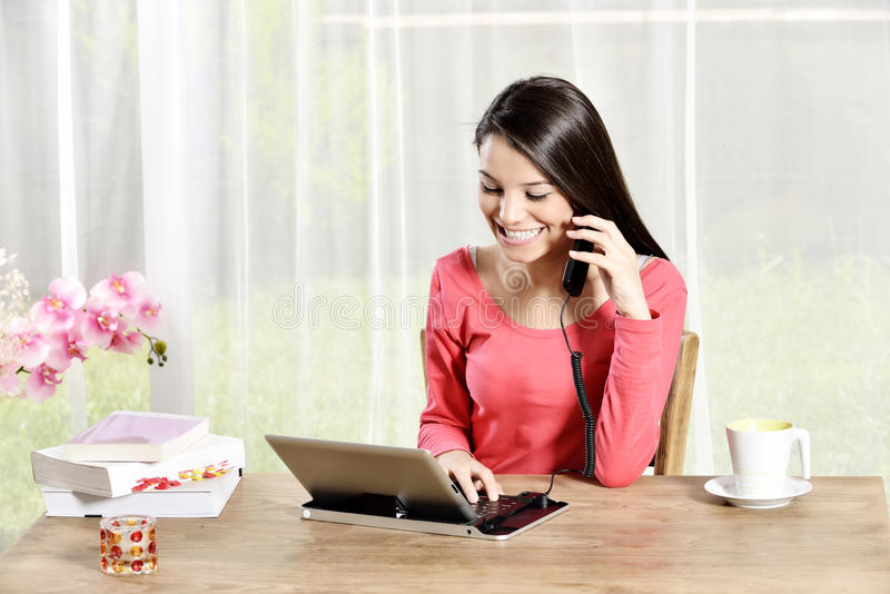 Young pretty woman work in home office. Young pretty woman holding Ipad looking and talking mobile phone stock image