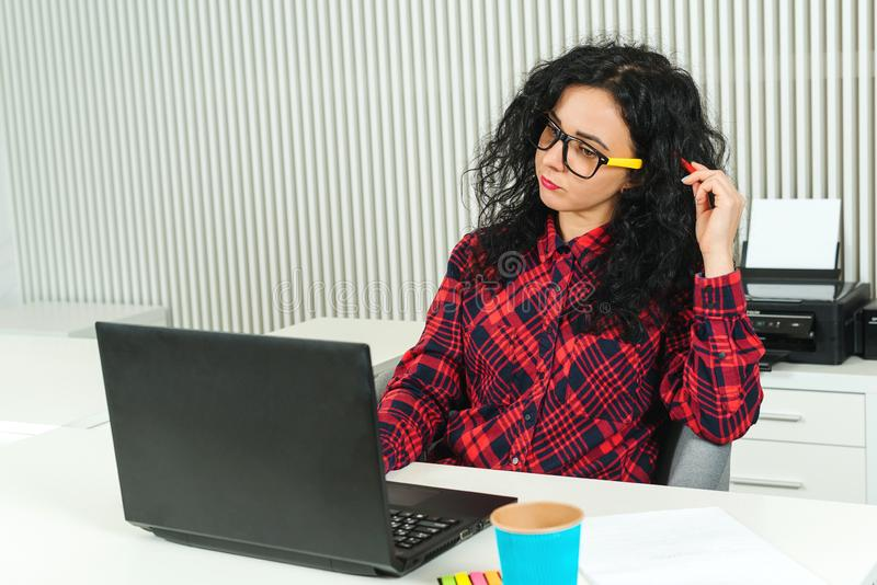 Young pretty woman working in modern office. Smart girl working with new startup. Worker woman in glasses concentrated on new idea stock photo