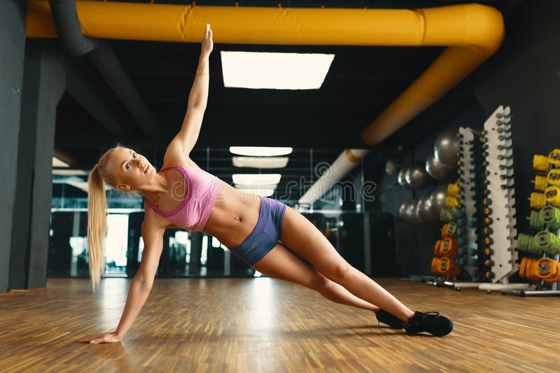Young pretty woman working out with personal weight in a modern. Young pretty woman, in attractive sports wears, pink top and mini blue shorts, working out with royalty free stock photography