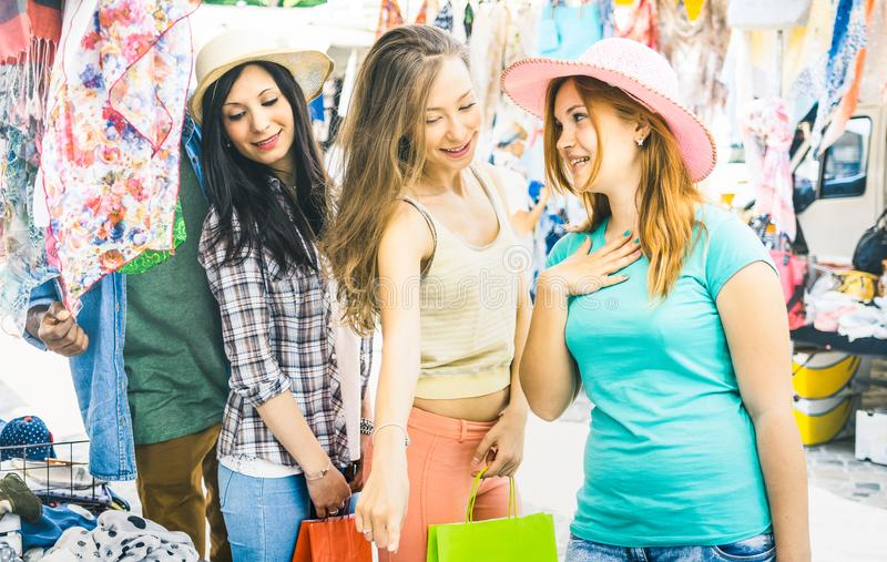 Young pretty women girlfriends at cloth flea market. Looking for fashion wardrobe - Friendship concept with female best friends having fun and shopping in old stock photo
