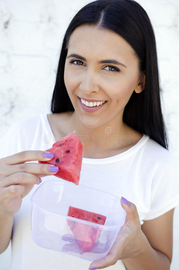 Young pretty women holding a slice of watermelon and smiling royalty free stock photography