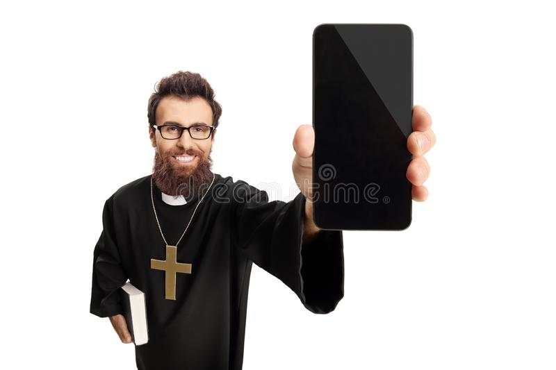 Young priest holding a mobile phone royalty free stock photography