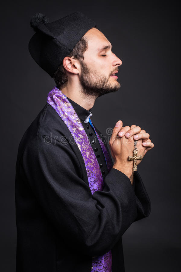 Young priest praying royalty free stock photography
