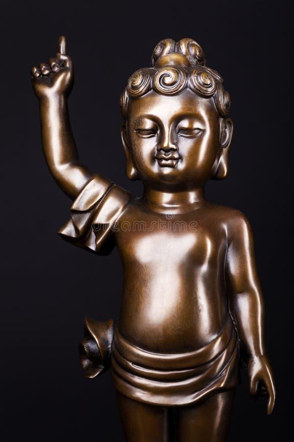 Young boy - prince Siddhartha Gautama. Young prince Siddhartha Gautama vith rized finger. The figure made of metal isolated on a black background royalty free stock image