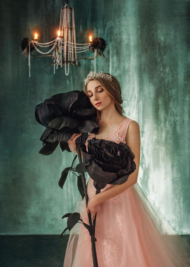 The young princess embraces fabulous, huge, black roses in the Gothic style. The girl has a crown and a luxurious, lush. Expensive, pink dress. Background is royalty free stock photo