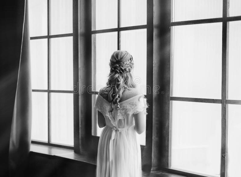 Young princess by large windows with bright sunlight waiting for knight. woman with creative hairstyle in vintage white royalty free stock image