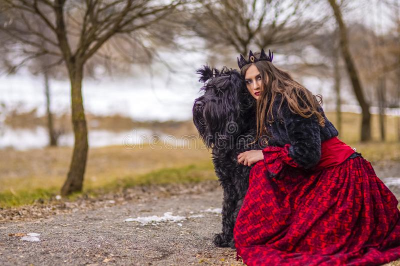 Young Princess in Red Dress And Black Fur Jacket Posing in Crown Along with Her Dog in Forest During Early Spring. Art Photography stock photo