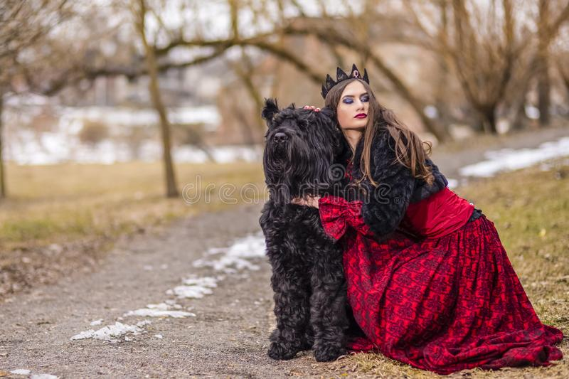 Young Princess in Red Dress And Black Fur Jacket Posing in Crown Along with Her Dog in Forest During Early Spring. Art Photography royalty free stock photography