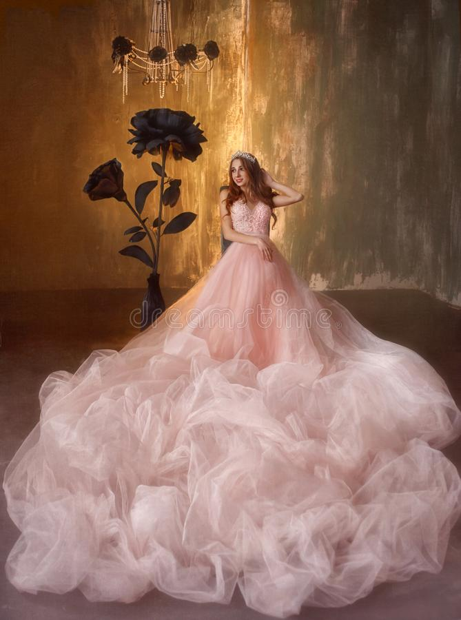 The young princess sits on a chair near the huge black roses in the Gothic style. The girl has a crown and a luxurious. Lush, expensive, pink dress with a very royalty free stock photo